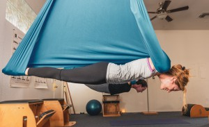 Aerial Yoga student in Vampire Pose at Go with the Flow Yoga Studio